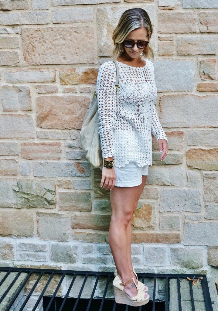 Neutral sweater, white shorts, tote, wedges, and sunglasses
