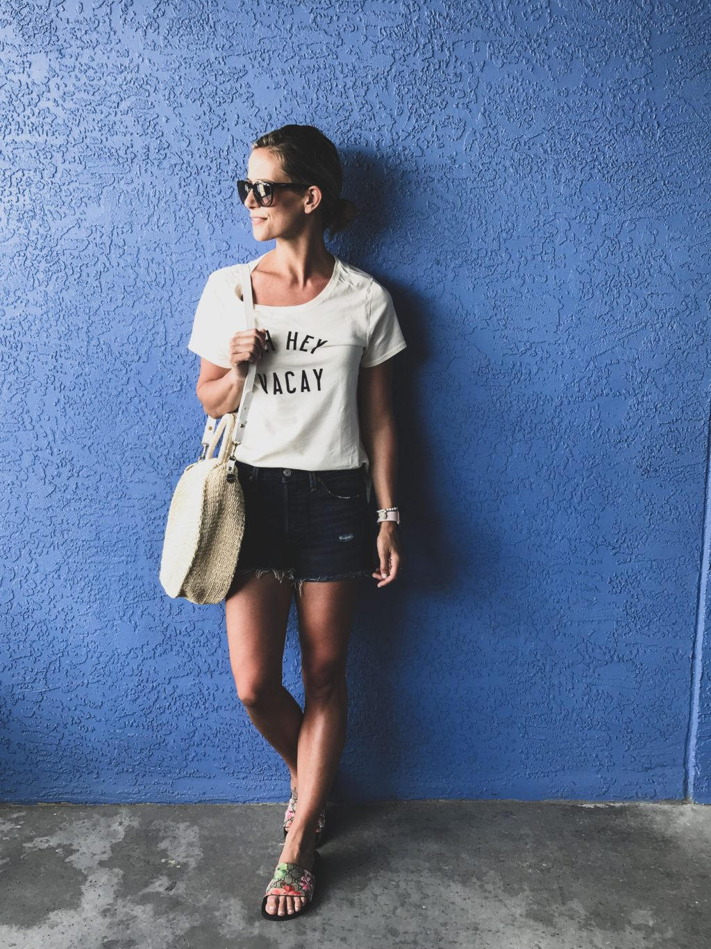 Beach vacation style, graphic tee, cut off shorts, straw tote, slides