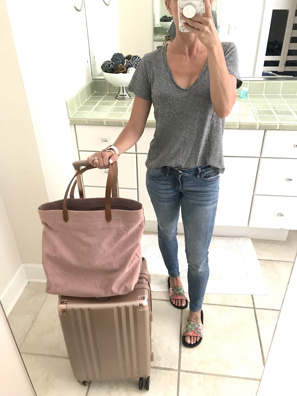 Beach vacation style, travel outfit--grey tee, denim, sandals, and pink tote