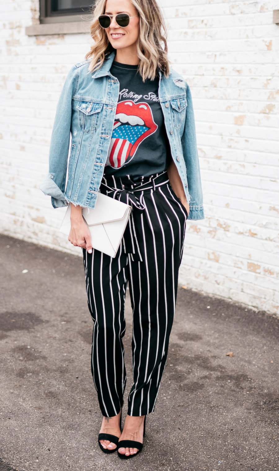 Band tee, striped pants, denim jacket, heels, clutch