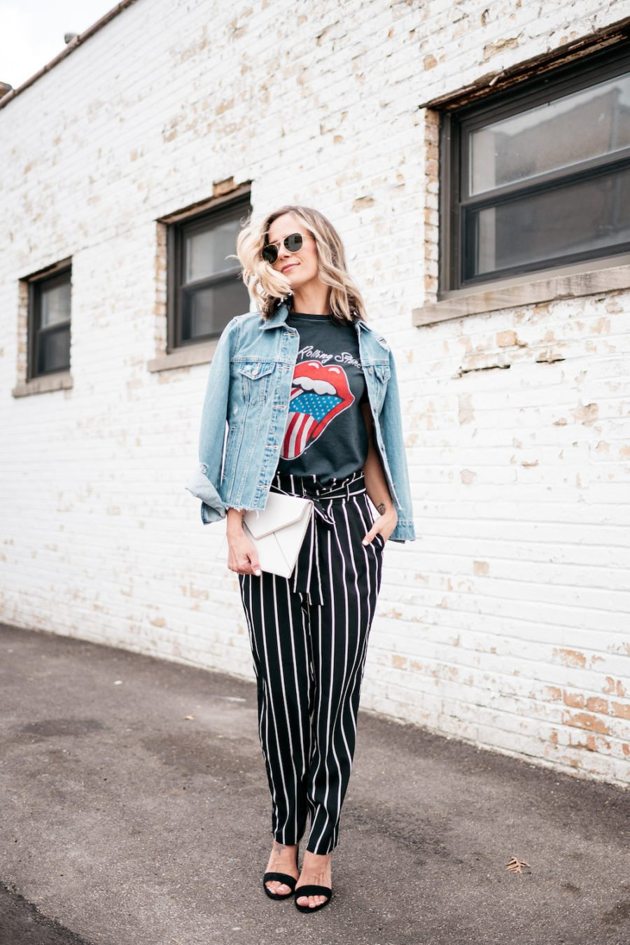 Band tee, striped pants, denim jacket, heels, clutch, sunglasses