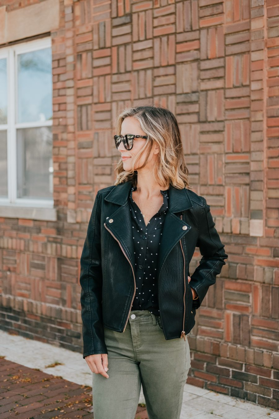 Budget friendly style: olive pants, polka dot blouse, moto jacket, booties, and sunglasses