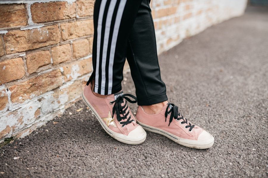 Adidas track pants and Golden Goose Deluxe brand sneakers