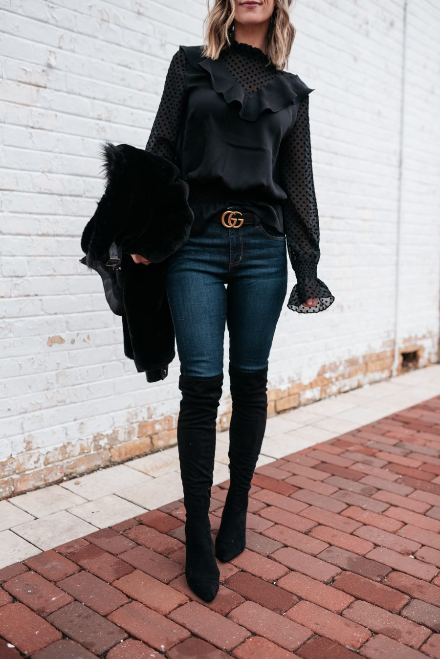 Faux fur jacket, black blouse, skinny jeans, and over the knee boots