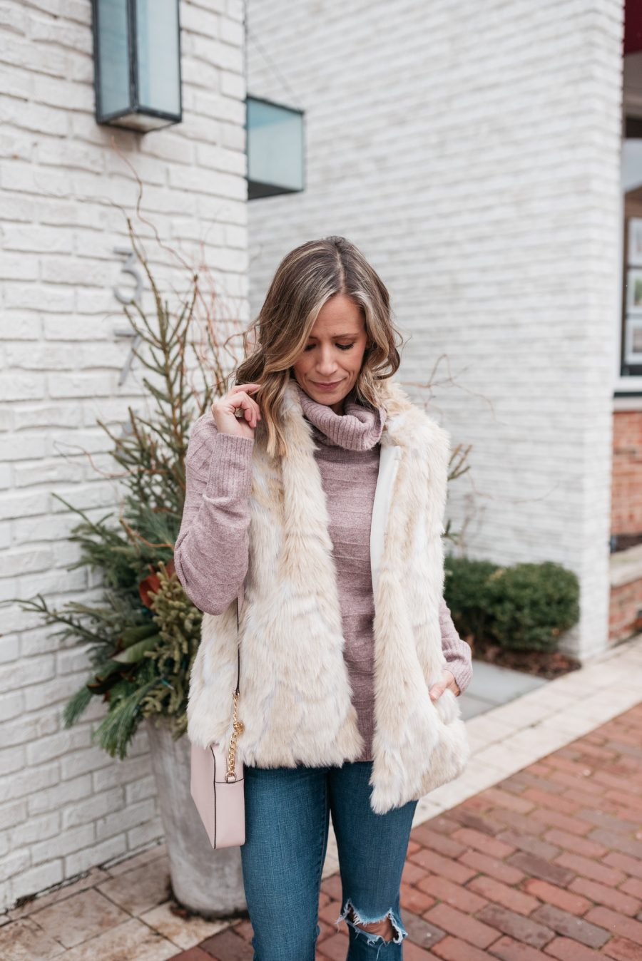 pink turtleneck, faux fur vest, skinny jeans, crossbody, and booties