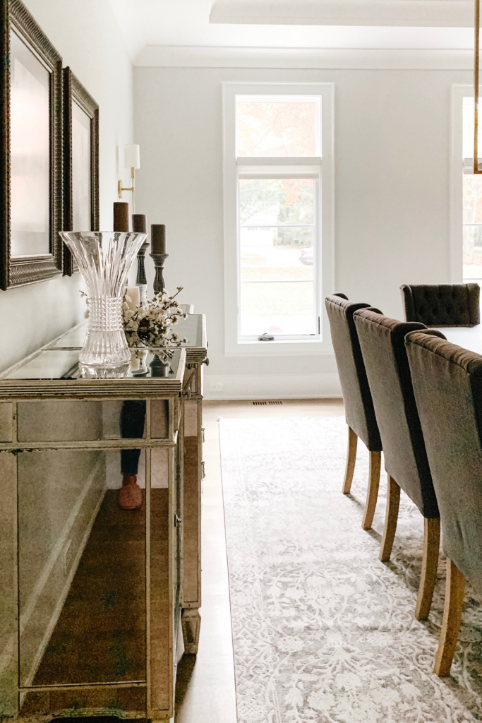 A warm and welcoming dining room of neutrals, comfortable seating, and beautiful accent lighting and art