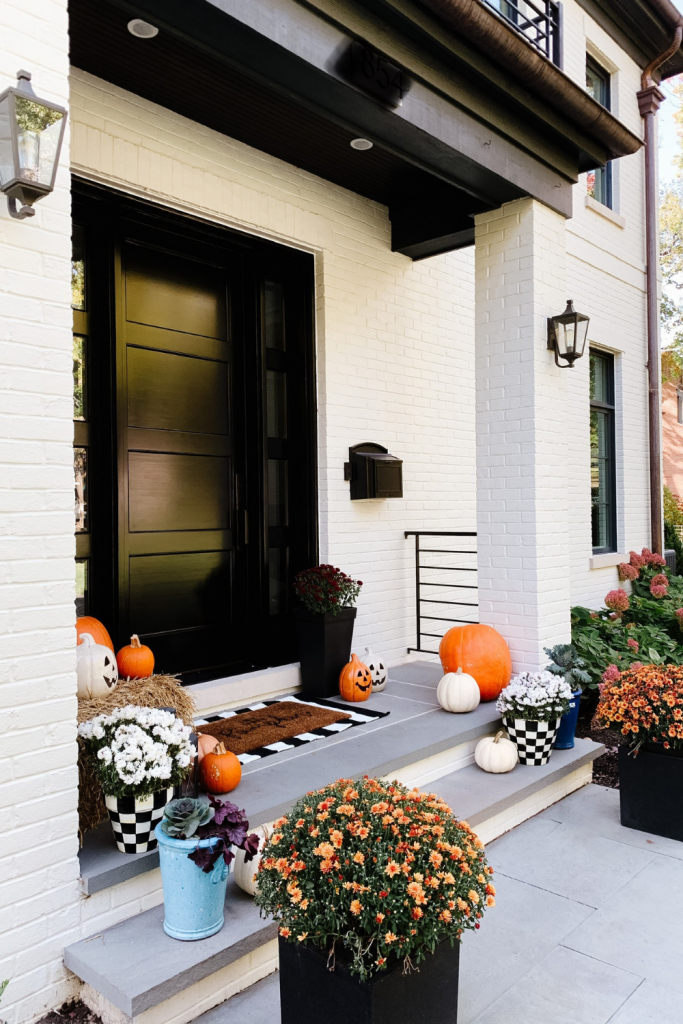 We gave our front porch a fall makeover complete with a freshly painted black door, pumpkins, mums, and a hay bail.