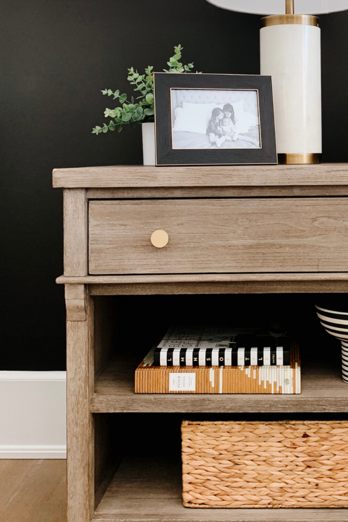 How to style a nightstand: lamp, table clock, framed pictured, basket, and books